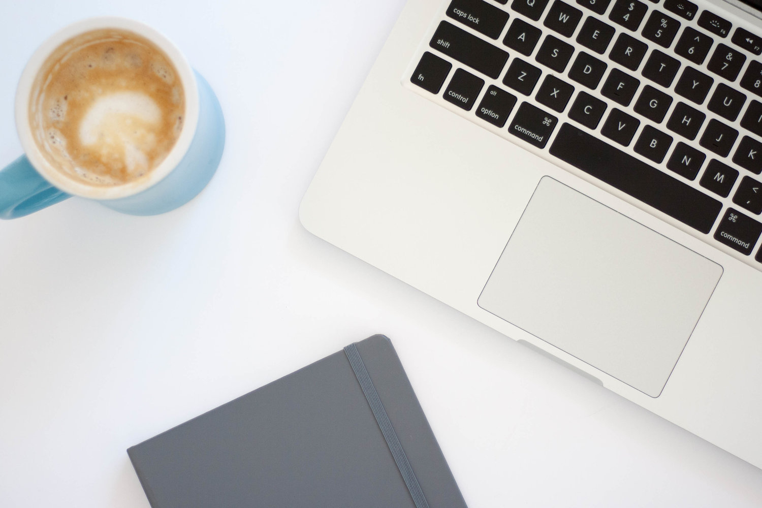 A mac laptop sits on a white table top next to a coffee cup and a notepad