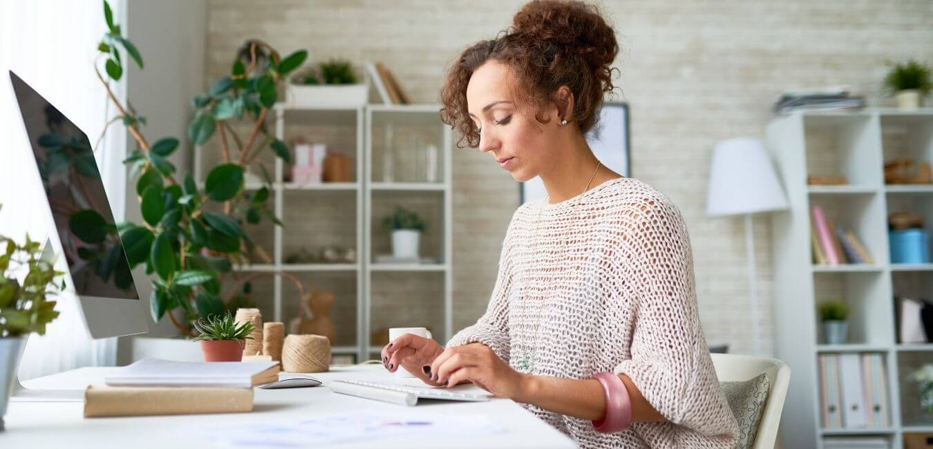 A remote executive assistant works at her desk.
