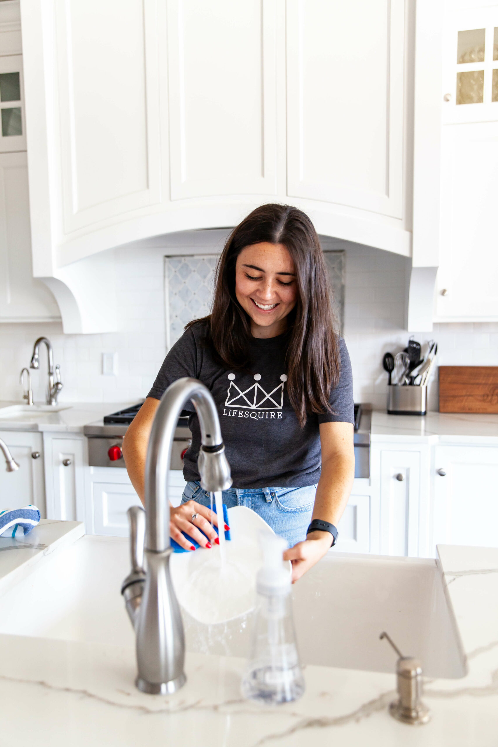 A woman with dark hair stands in a kitchen rinsing a bowl in a sink